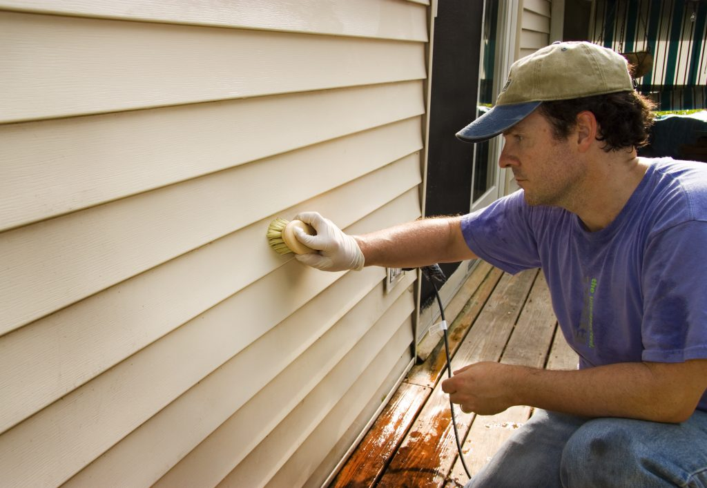 man washing house's siding by hand with a brush